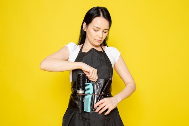 ブラシ波ハサミを取って白いtシャツ黒マントの正面の若い女性美容師
