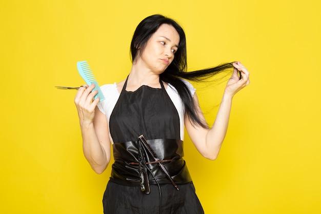 正面を洗った髪をブラッシングし、黄色の背景のスタイリスト理髪店でポーズをとって彼女の髪をカットブラシで白いtシャツブラックケープの美しい女性美容師