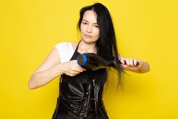 黄色の背景のスタイリスト理髪店でポーズをとって彼女の髪をブラッシング洗髪乾燥ブラシで白いtシャツブラックケープの正面の美しい女性美容師