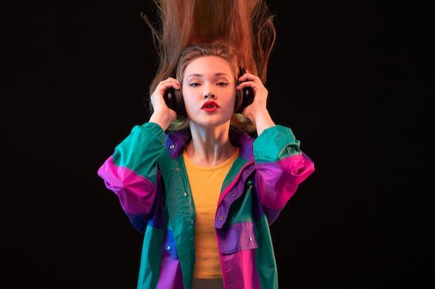 黒の背景ダンスモダンファッションでポーズ黒いイヤホンでカラフルなコートオレンジtシャツで正面現代の若い女性