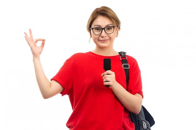 白に笑みを浮かべてマイクを持っている黒いバッグを着ている赤いtシャツの正面の若い女子学生