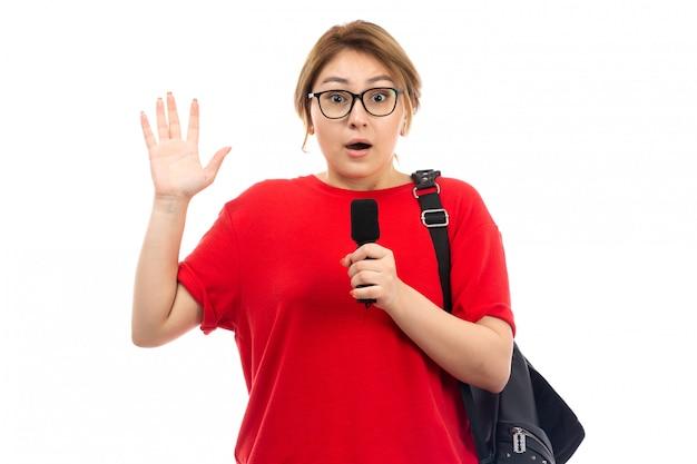 白で驚いたマイクを保持している黒いバッグを着ている赤いtシャツの正面の若い女子学生