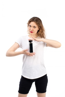 白に黒のチューブを保持している白いtシャツ黒のショートパンツの正面の若い女性