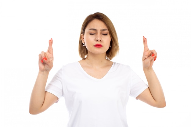 正面を向いた白いtシャツポージングで若い女性が指を閉じて白目を閉じた