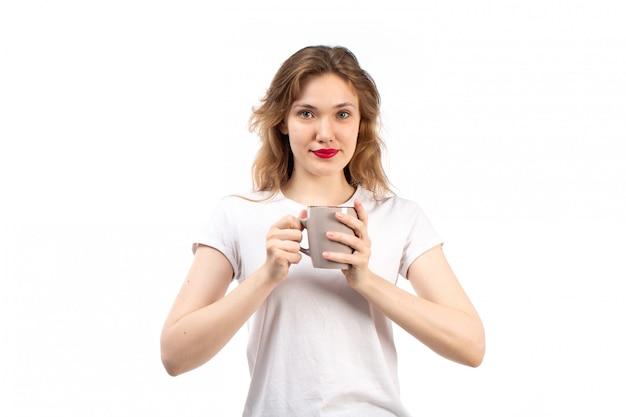 白のホールディングカップを笑顔白いtシャツの正面の若い女性