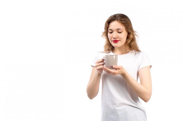 白の紅茶とホールディングカップを笑顔の白いtシャツで正面の若い女性