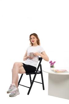 白の上に座ってお茶とホールディングカップを笑顔白いtシャツの正面の若い女性