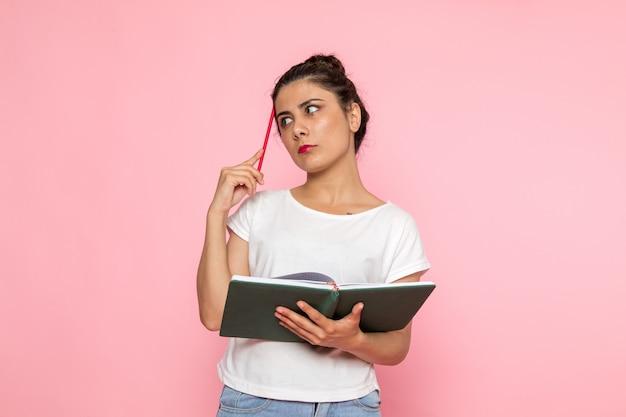 白いtシャツと思考のコピーブックを保持しているブルージーンズの正面の若い女性