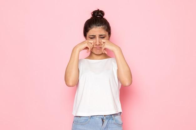白いtシャツとブルージーンズのポーズと偽の泣き声の正面の若い女性