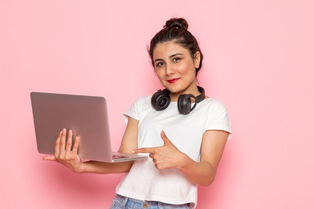 白いtシャツとブルージーンズのイヤホンでラップトップを使用して正面の若い女性