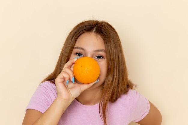 ピンクのtシャツとオレンジを保持しているブルージーンズの正面の若い女性