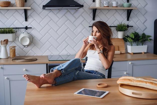 居心地の良いキッチンの自宅の椅子でリラックスしながらタブレットコンピューターを使用して白いtシャツで陽気な女の子。