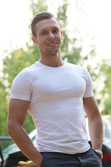 白いtシャツを持つハンサムな男