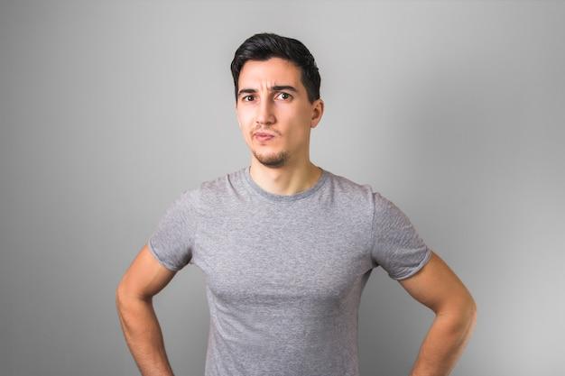疑問を持つ灰色のtシャツでハンサムな男