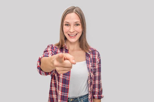 素敵でポジティブな若い女性が立ってポイントします。彼女は微笑みます。モデルは白いtシャツとチェロシャツを着ています。