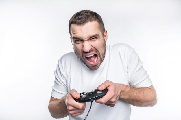 白いtシャツを着た男が白い背景の上のゲームコンソールで遊ぶ