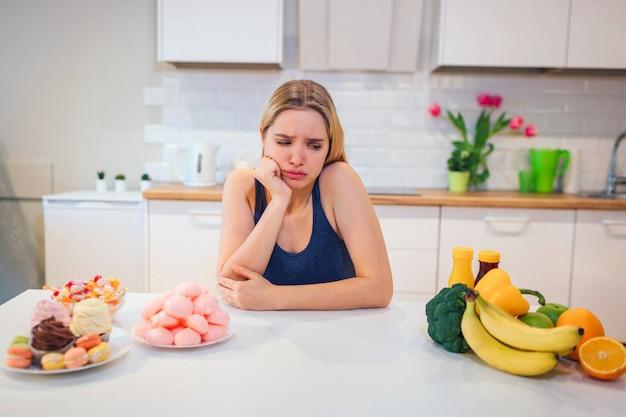 国会闘争。キッチンで新鮮な果物野菜やお菓子の間を選択する青いtシャツの若い悲しい女性。健康食品と不健康食品の選択。ダイエット。健康食品