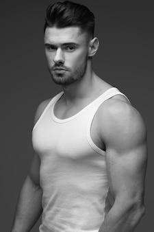 若い筋肉男。ひげを持つ若い男。 tシャツを着た男性。灰色の背景に男性の肖像画。スタイリッシュな男。黒と白の写真。スポーツ男。男性フィットネスモデル。スタジオポートレート