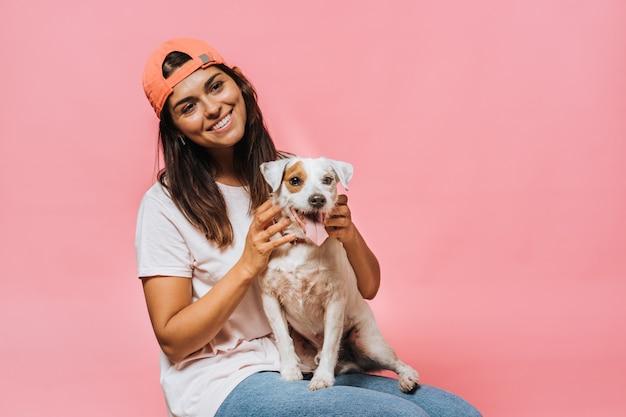 オレンジ色の野球帽をかぶった女性は、薄いピンクのtシャツとジーンズを着て、膝の上に座っている犬の首をなで、美しい笑顔で脇を見ながら夢を見ていた。幸福と夢