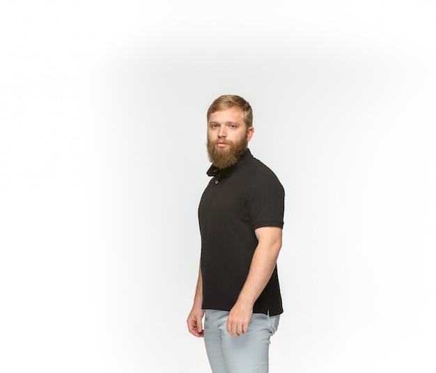 白で隔離される空の黒いtシャツで若い男の体のクローズアップ