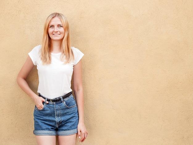 空白の白いtシャツと粗い通りの壁、ミニマルな都市服スタイルに対してポーズジーンズを着て内気な少女