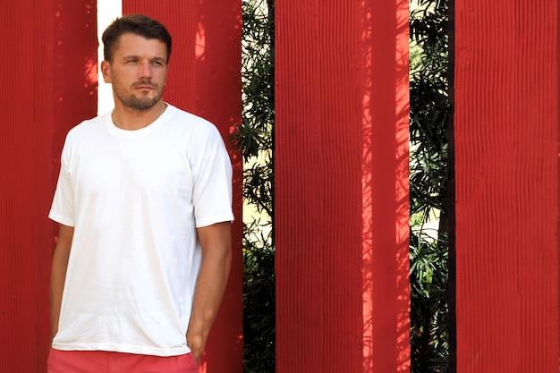 路上で白いtシャツのサンゴのショートパンツを着ている男のライフスタイルの肖像画。赤い壁の背景。ドミニカ共和国の夏。