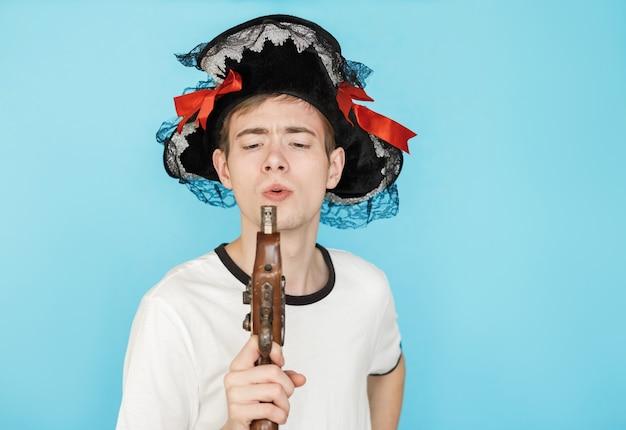 海賊の帽子と手に銃で白いtシャツの若い面白い男性ティーンエイジャーが煙を吹く