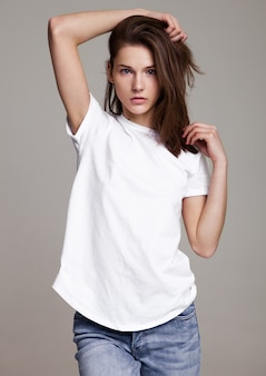灰色の背景にポーズをとって若い美しいファッションモデルとモデルテストの肖像画。白いtシャツとジーンズを着ています。