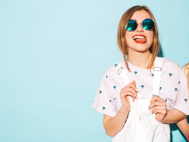 探している若い美しい女性。丸いサングラスで彼女の舌を示すカジュアルな夏の黄色のtシャツ服のトレンディな女の子。ポジティブな女性は顔の感情を示します。青に分離された面白いモデル