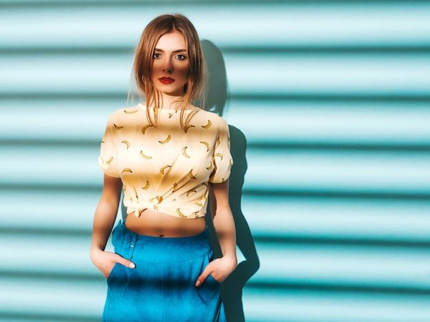 探している若い美しい女性。カジュアルな夏の黄色のtシャツの服でトレンディな女の子。水色の壁に近いポーズモデル
