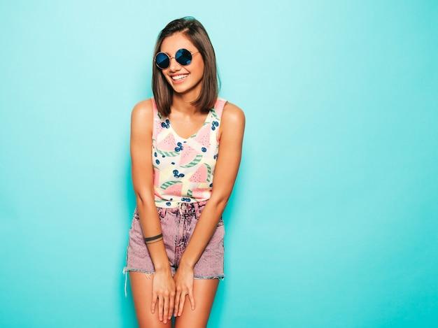 カメラを見て若い美しい女性。ラウンドサングラスのカジュアルな夏の白いtシャツとジーンズのショートパンツでトレンディな女の子。肯定的な女性は顔の感情を示しています。青に分離された面白いモデル