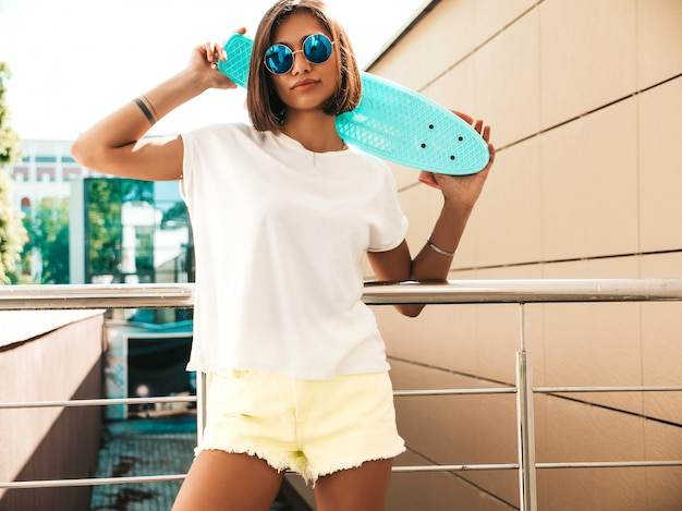 サングラスの若い美しいセクシーな笑みを浮かべて流行に敏感な女性。夏のtシャツとショートパンツのトレンディな女の子。通りの背景にポーズをとって青いペニースケートボードと肯定的な女性