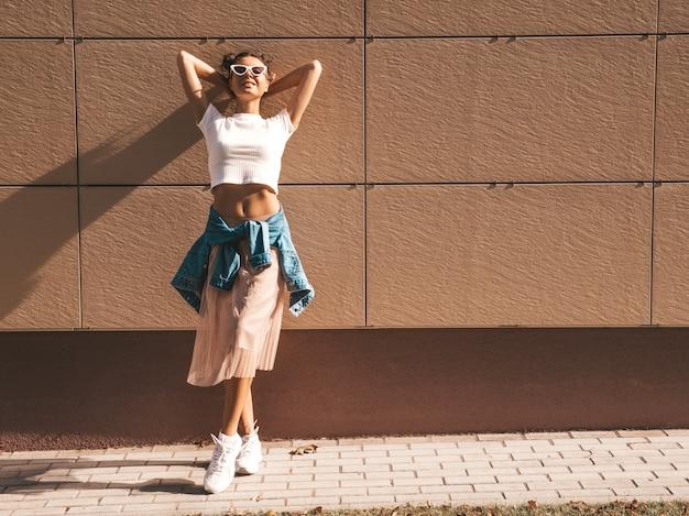 夏の流行に敏感な白いtシャツ服に身を包んだ角髪型と美しい笑顔モデル。壁の近くの通りでポーズをとってセクシーな屈託のない少女。サングラスで楽しんでトレンディな面白いと肯定的な女性