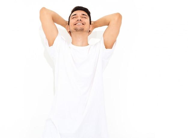 ジーンズ服とtシャツのポーズに身を包んだハンサムな笑顔若いモデル男の肖像。彼の頭に触れる