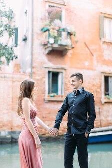 イタリアのヴェネツィアの古い建物の背景に立っている美しいカップル、ピンクのドレスの女の子と黒いtシャツの男
