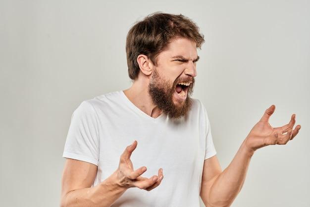 Tシャツにひげを生やした若い男性は、さまざまな感情、楽しみ、悲しみ、怒りを示します