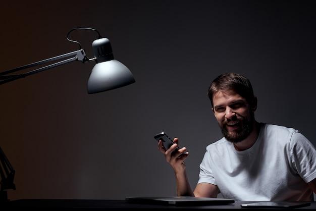ラップトップと電子タブレットを備えた白いtシャツを着た男性がテーブルで働いています