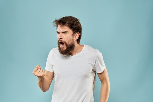 Tシャツにひげを生やした若い男性が壁にさまざまな感情、楽しさ、悲しみ、怒りを示している