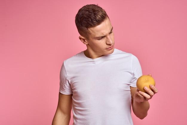 ピンクの壁に白いtシャツを着た果物を持つ男、男は手に持った