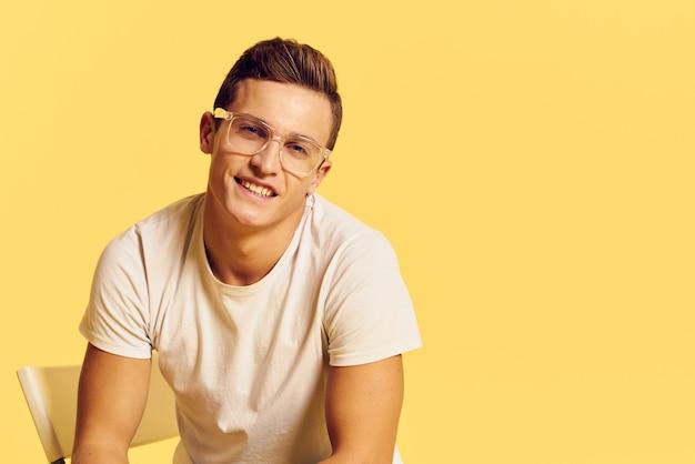 ジーンズと薄黄色の壁に白いtシャツでポーズをとる男性モデル