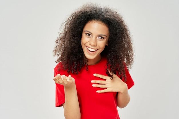 色付きの表面のポーズのスタジオでtシャツの女性アフリカ系アメリカ人