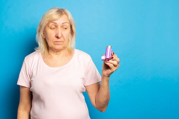 カジュアルなtシャツを着たフレンドリーな老婆の肖像画は吸入器を持ち、孤立した明るい壁でそれを見ています。感情的な顔。喘息、アレルギーの概念
