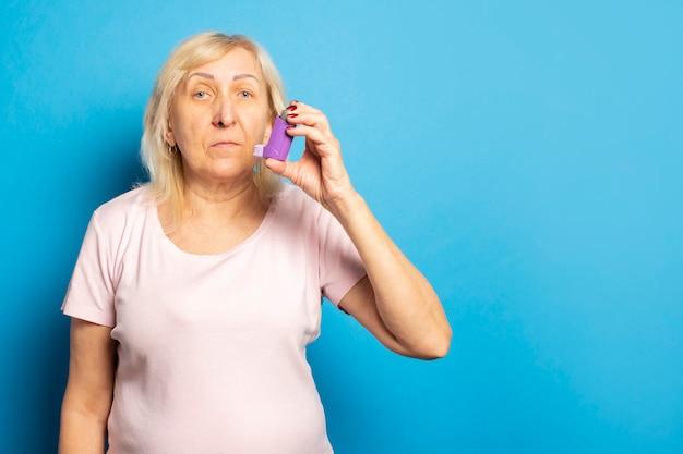 孤立した光の壁に吸入器を保持しているカジュアルなtシャツのフレンドリーな老婆の肖像画。感情的な顔。喘息、アレルギーの概念