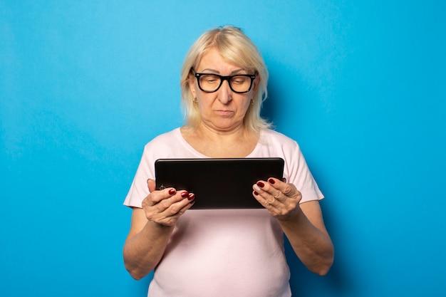 メガネで深刻な顔をしたフレンドリーな老婦人と彼女の手でタブレットを持ち、孤立した青い壁に画面を見ているカジュアルなtシャツの肖像画。感情的な顔