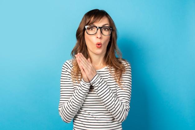 カジュアルなtシャツと光のメガネで驚いた顔を持つ若いフレンドリーな女性の肖像画