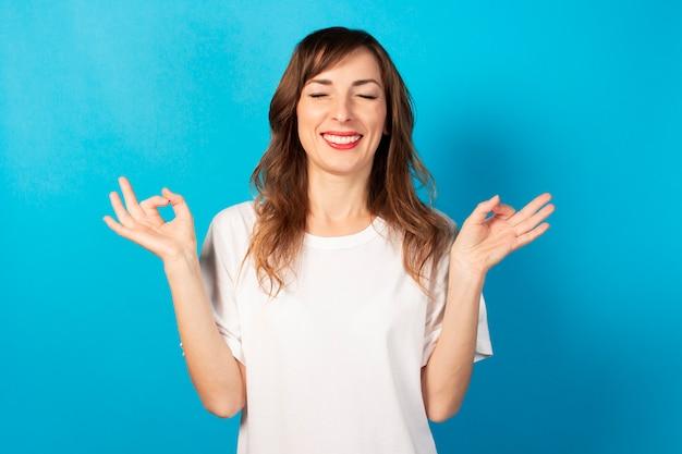 目を閉じて白いtシャツでかわいい若い女性は彼の手のヨガ、集中力、孤立した青の瞑想でジェスチャーになります。瞑想、夢、計画、良い気分のコンセプト