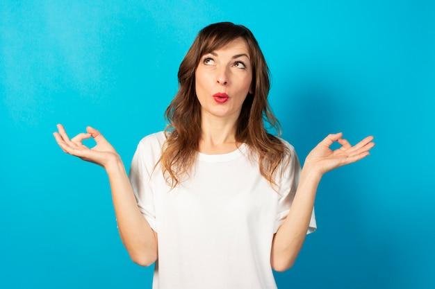 瞑想のジェスチャーと青に驚いた顔でカジュアルなtシャツのフレンドリーな若い女性の肖像画、リラックス