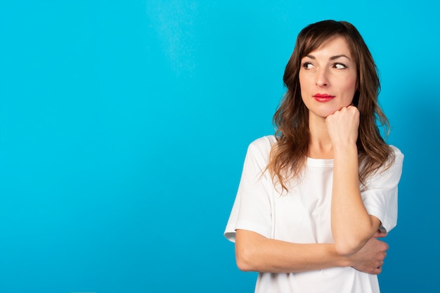 カジュアルなtシャツのフレンドリーな若い女性の肖像画は彼女のあごの下に手を保持し、青に目をそらします