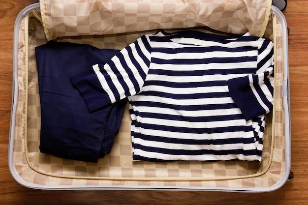ブルーのストライプと道路のスーツケース、トップビューで青いパンツ付きtシャツ