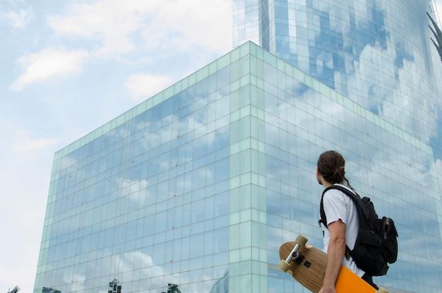 黒い髪と白いtシャツとオレンジ色のロングボードと黒いバッグの男の背面図。スペイン、バルセロナのビーチ近くの大きな建物を探しています。